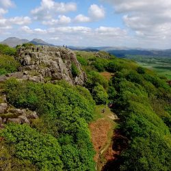 This aerial shot caught climbers pear off a cliff face peaking out the top of a lush woodland in North Wales.
