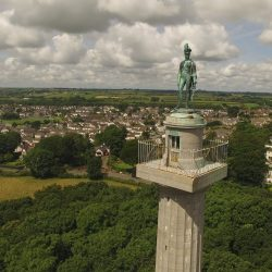 A drone shot of Marquess of Anglesey's Column with the River Menai seen in the background.